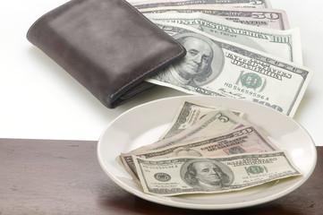 Dolares en placa con billetera en fondo blanco