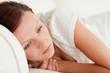 Sad woman lying on a bed
