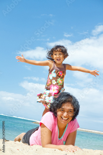 ethnic girl fun with mother on tropical beach