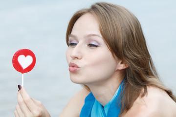 Молодая красивая женщина ест конфеты леденцы на белом фоне.