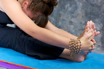 close up of woman doing a yoga forward fold or Paschimottasana