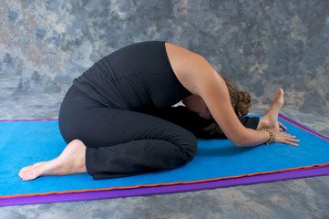woman on mat in studio doing yoga pose Janu Sirsasana or Knee to
