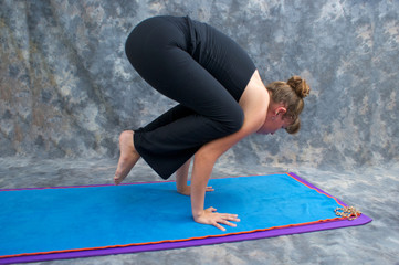 woman balancing on mat in studio doing yoga posture Bakasana or