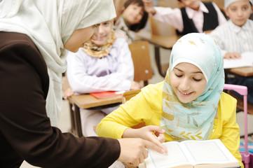 Female teacher helping children in classroom