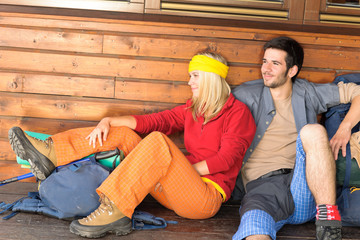 Tramping young couple backpack relax by cottage