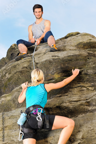 Woman climbing up rock man hold rope