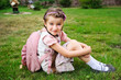 Young school girl with pink bagpack sits on grass
