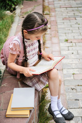 Young school girl with pink bagpack sits reading the book