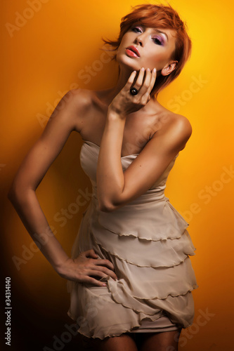Fashion photo of beautiful redhead girl posing in sensual dress