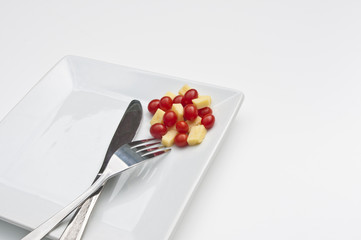 Chese and tomatoes on a white plate with a knife and fork