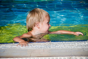 happy young smiling boy in the swimming pool