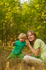 Active baby in nature with mother
