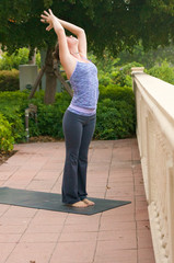 woman doing yoga posture sun salutation  outdoors in public on m