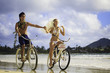 newlyywed couple on the beach with their bicycles