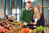 Couple Buying Groceries with List on Phone
