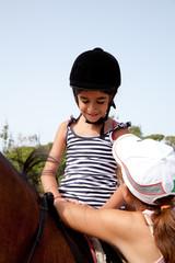 bambina che sale a cavallo