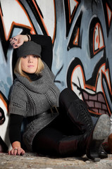 Junge Frau sitzend vor Grafittiwand