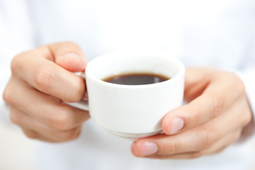 a woman drinkig a cup of coffee