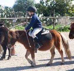 bambina sopra pony