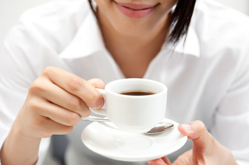 a woman drinking a cup of coffee