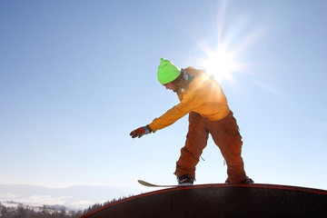 Snowboarder jumping against sunset