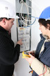 Two electricians repairing fuse box