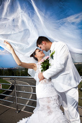 newly married couple covered with long white veil