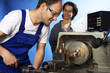 Two technicians on lathe machine in workshop