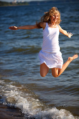 Happy woman jumping on the sea beach
