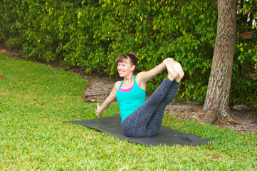 smiling woman doing Yoga pose Navasana variation or boat pose ou