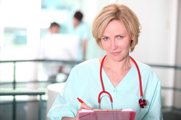 Nurse writing on clip-board