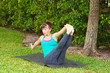 woman doing Yoga pose Navasana variation or boat pose outdoors o