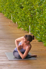 woman doing Yoga pose rotated pigeon outdoors in morning