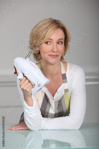 Blond woman holding electric whisk