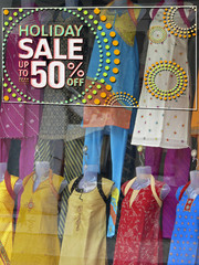 window display with 50 % Discount board at a shop, India