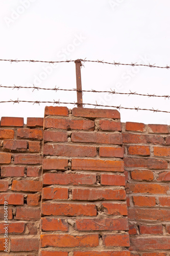red brick wall with the barbed wire