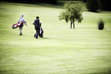 Men walking at golf course with bags.