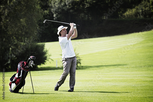 Golfer pitching at golf course.