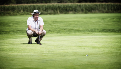 Golfer analysing green before putting.