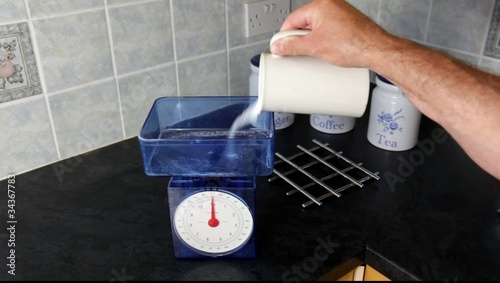 Weighing sugar on a kitchen scale for home baking.