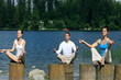 Three people meditating on wooden stump by the lake