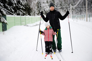 Father and daughter enjoy skiing in rural area on winter day