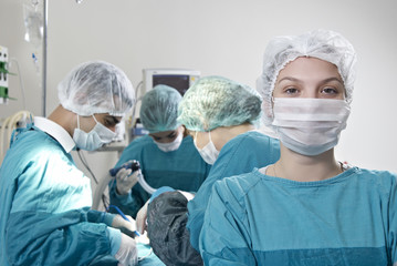 Female doctor in surgery with a group of doctor