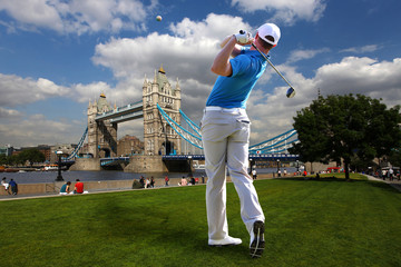 Man playing golf next to Tower Bridge, London, UK