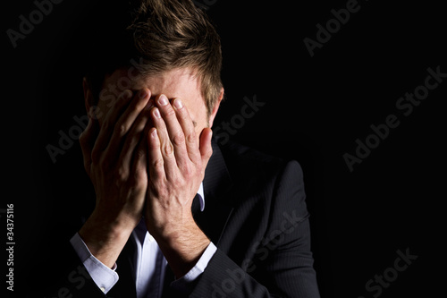Desperate businessman covering his face.