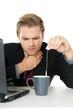mann mit halsschmerzen auf arbeit tee trinken