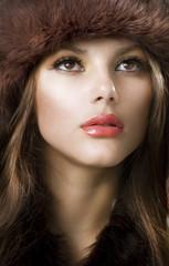 Beautiful Young Woman wearing Fur Hat. Winter Style