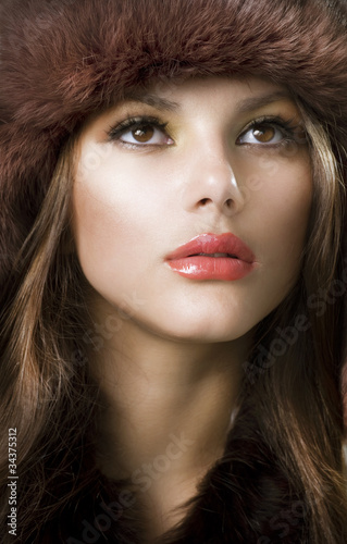 Beautiful Young Woman wearing Fur Hat. Winter Style