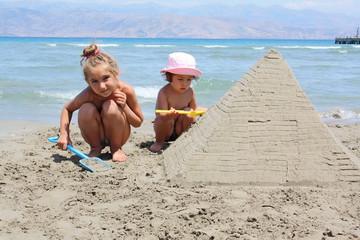 children make sandy pyramid