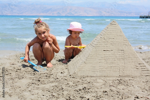 children make sandy pyramid
